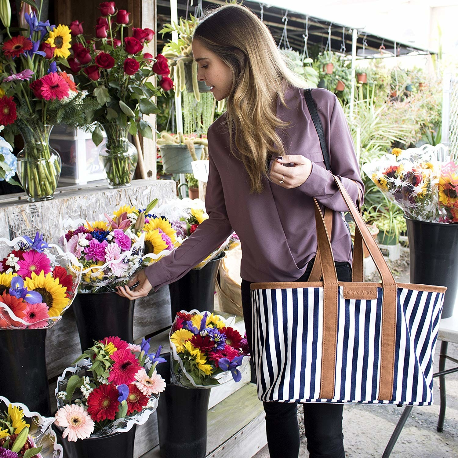 model holding the blue and white striped bag with brown edge and handles