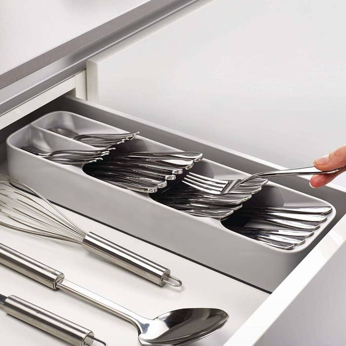 A hand putting a fork into the rectangular organizer; it has four slots at diagonal angles, one stacked on top of the next, with wide-mouth openings