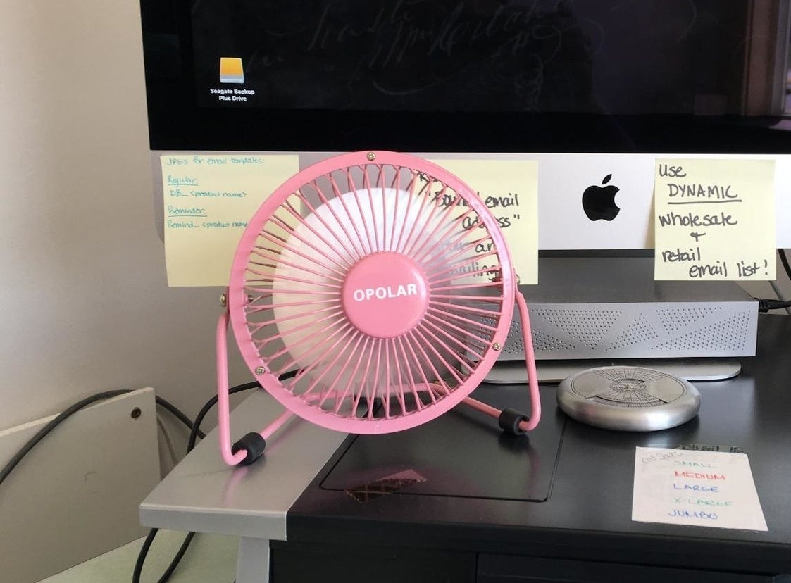the pink desk fan on a desk in front of an apple monitor