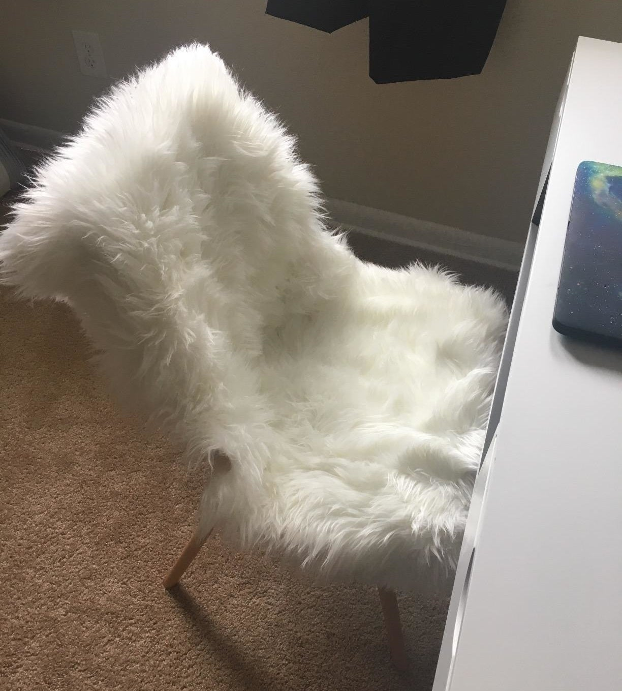 a reviewer's image of the faux fur rug draped over a desk chair
