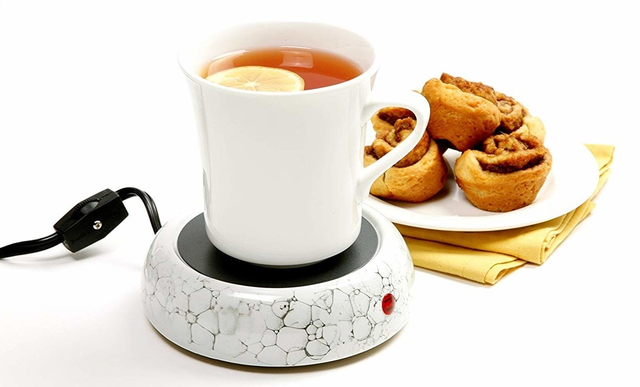 a mug on the mug warmer next to a small plate of pastries