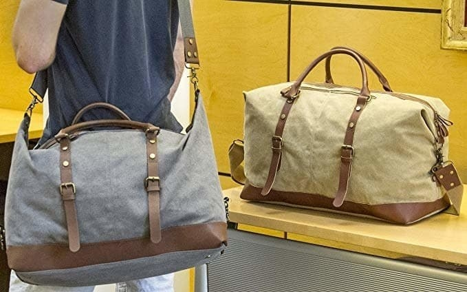 A person is holding a grey canvas duffle bag around their shoulders with another beige one next to them