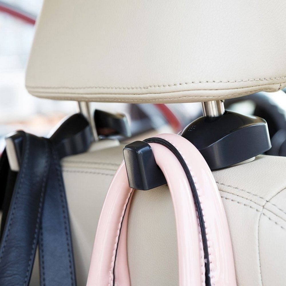 A headrest, raised a little to fit the hooks, which attach to the metal poles on either side of the rest; a bag hangs from each hook over the back of the seat