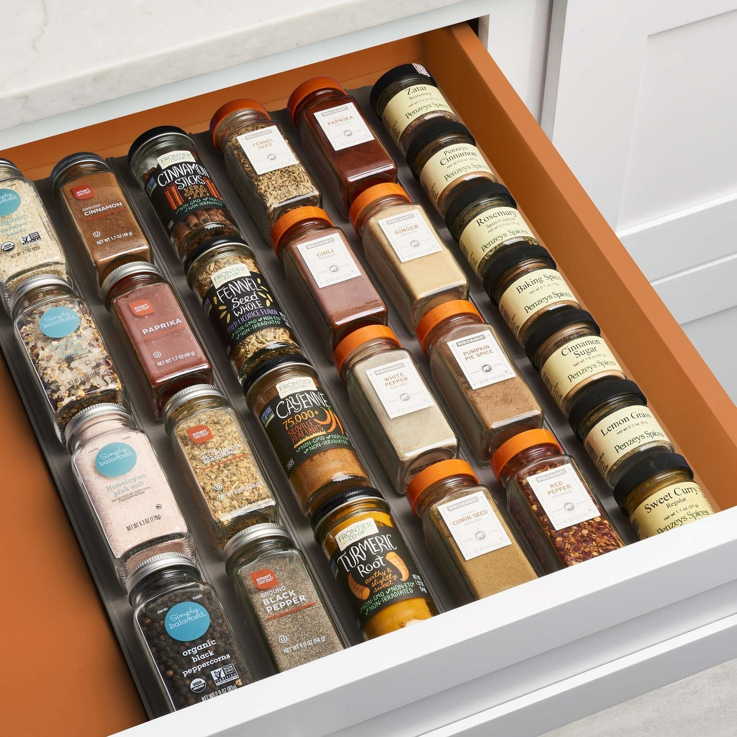A drawer with six of the narrow rubber mats/columns next to each other, each column with four-plus bottles of spices laid end to end so the overall effect is a flat lay grid of spices