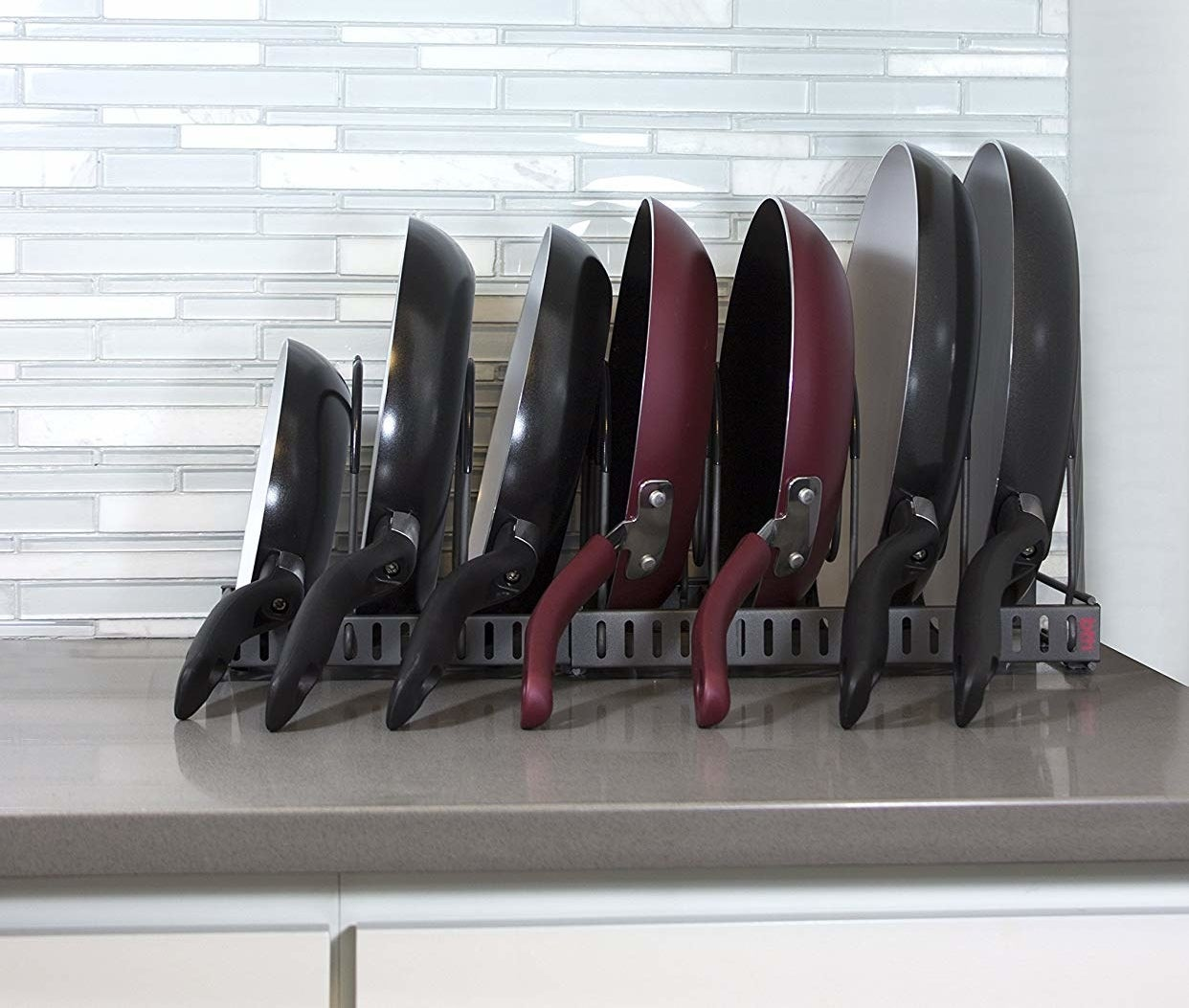 the rack with seven skillets stacked on their sides of graduating sizes; the thick wire dividers keep the pans about an inch apart from each other
