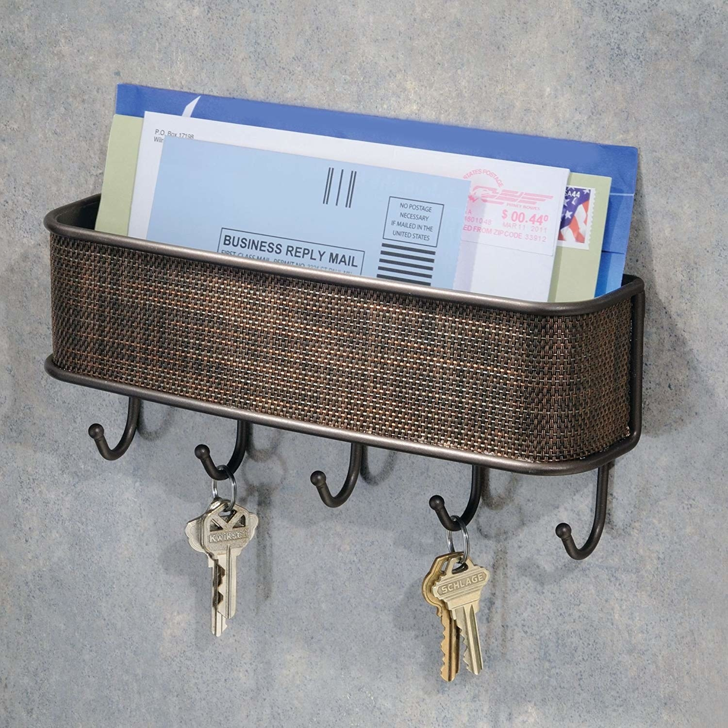It has a basket for mail to sit in on top; the front is covered with a brown basketweave pattern; and there are five small hooks for keys at the bottom