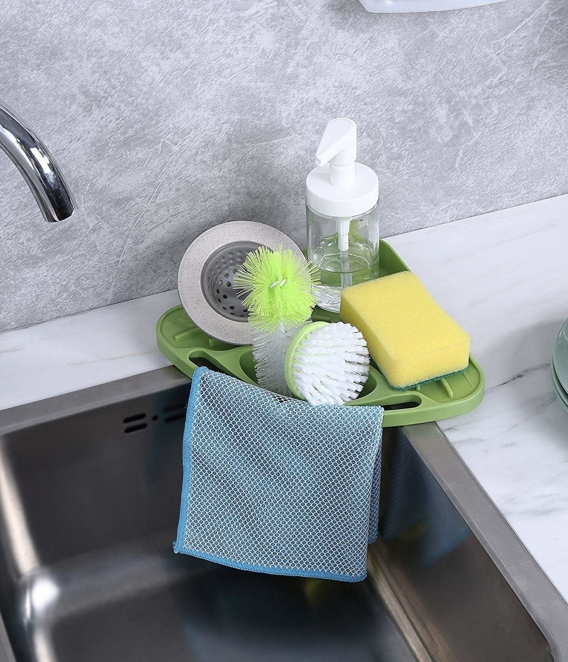 the tray, stacked with a soap pump, a sponge, two scrubber brushes, a catcher for the drain, and a scrub cloth, on the corner of a sink