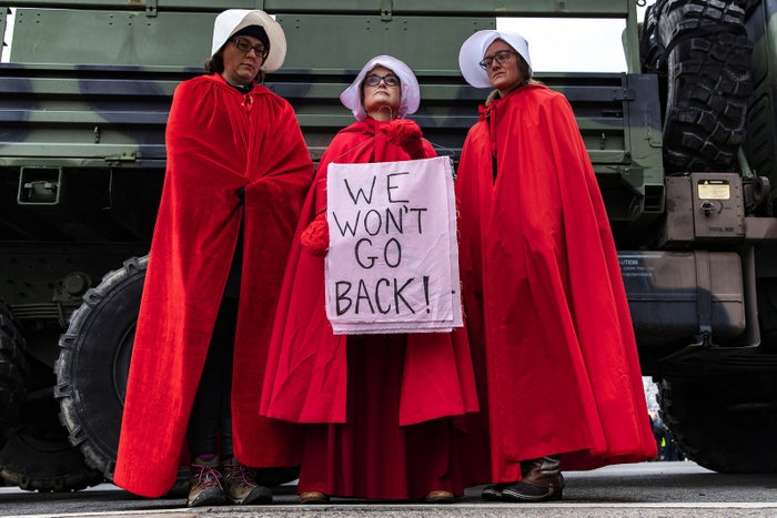 Demonstrators dressed in Handmaid's Tale costumes hold a sign at the third annual Women's March in Washington, DC, on Jan. 19.