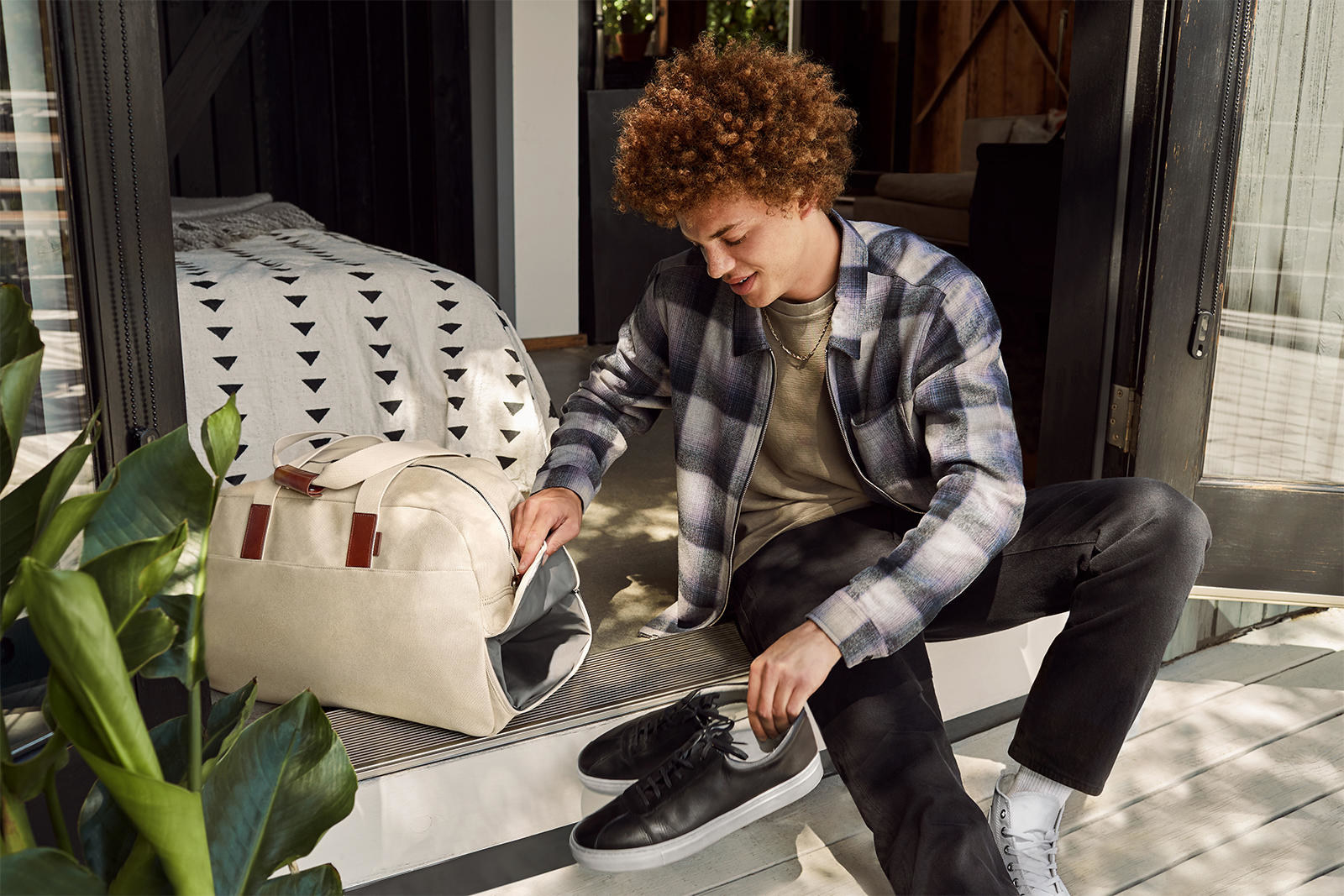 Model is putting black shoes into the shoe compartment of the cream colored duffle bag