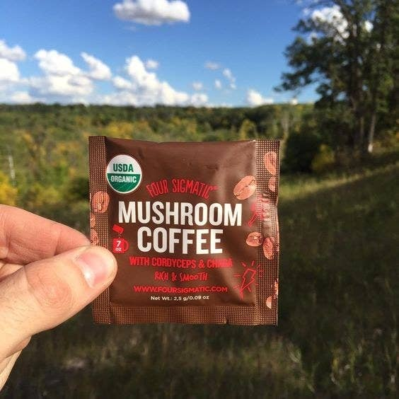 Reviewer holding up a packet of the mushroom coffee mix