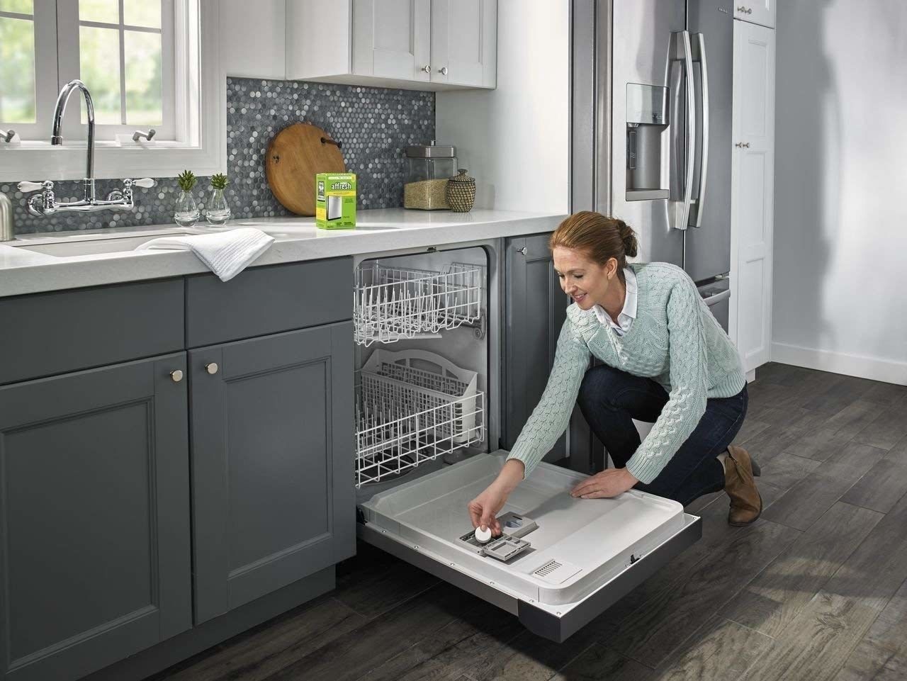 Model puts small tab of cleaner into empty dishwasher