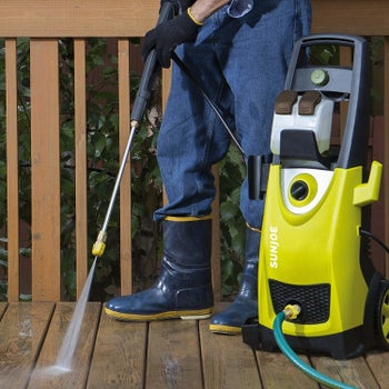 someone using the power washer on a wooden deck