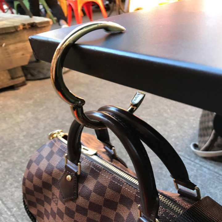 reviewer image of clip holding purse on end of table
