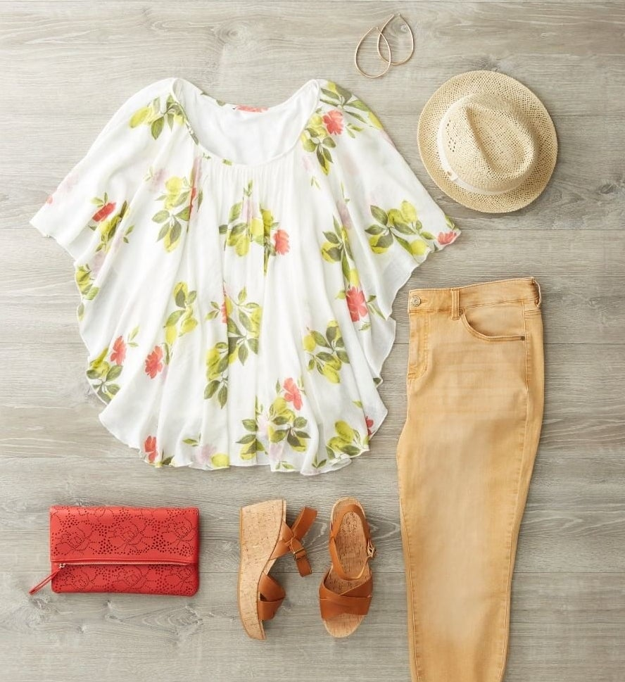 Flatlay of a floral top, tan denim pants, wedge sandals, straw hat, gold hoop earrings, and a small red purse