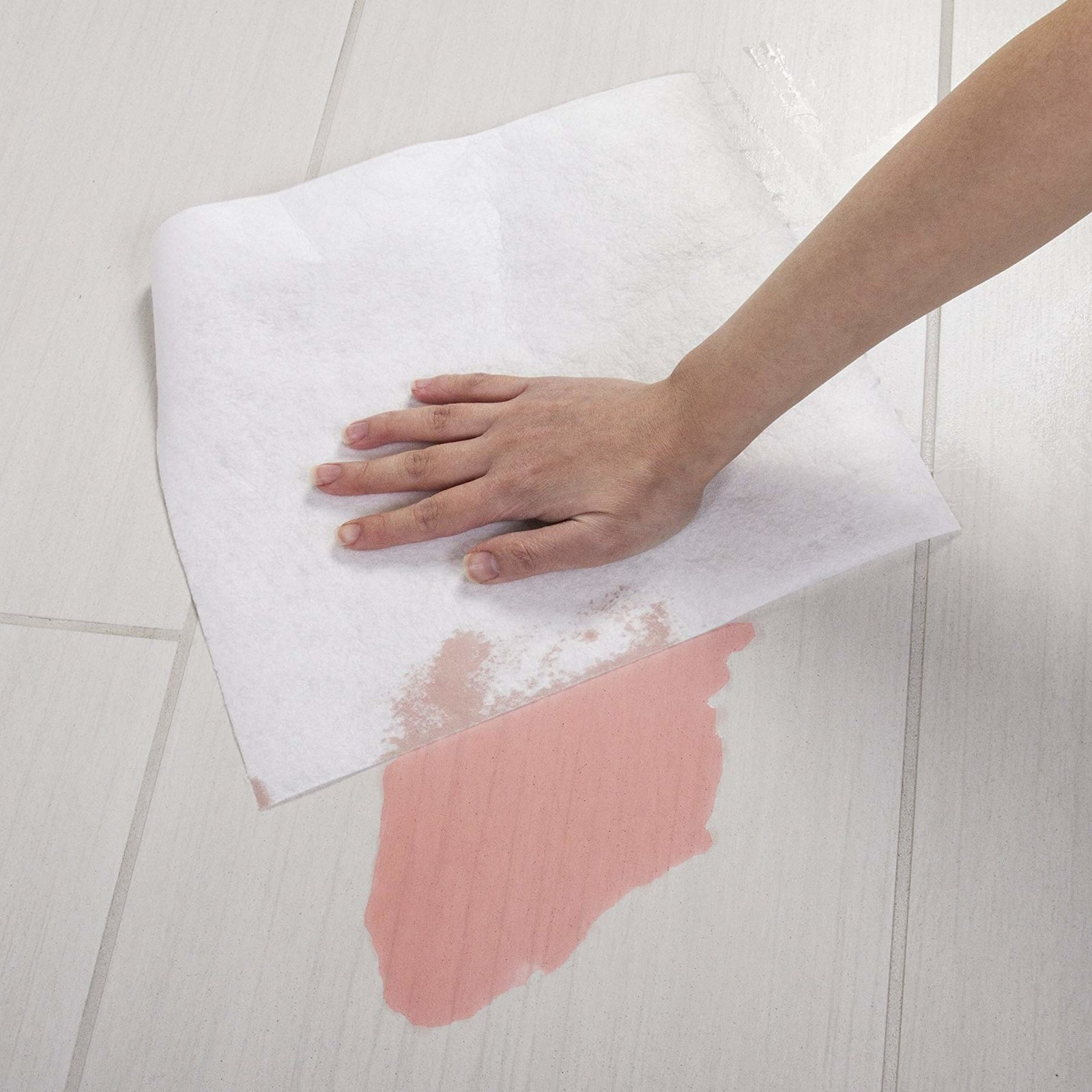 person wipe up a red liquid with the reusable bamboo paper towel