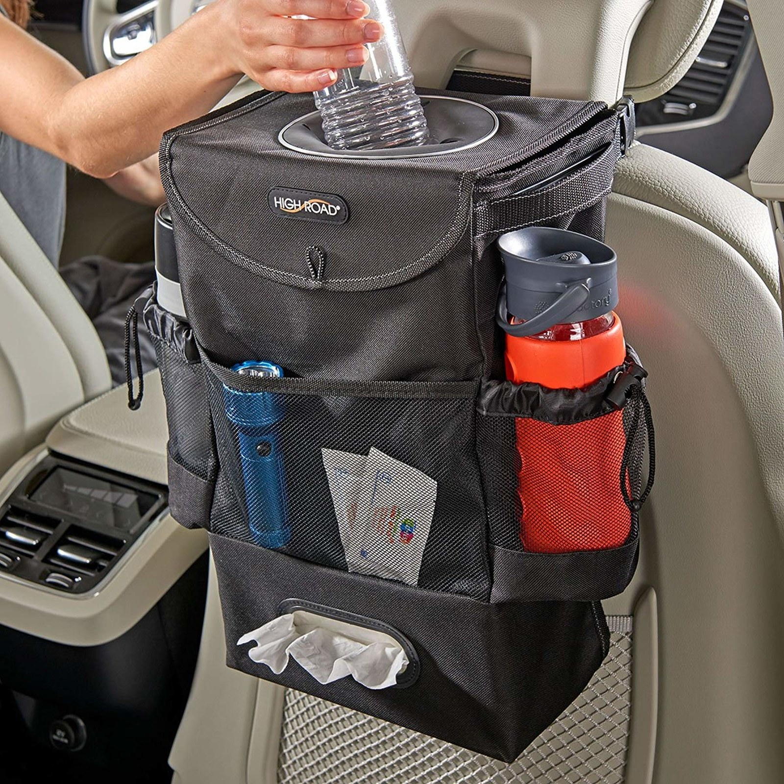 the car storage bag mounted to the back of the passenger seat with a hand putting a bottle into the top compartment, side pockets with water bottles inside, and we wipes peeking out of a dispenser along the bottom