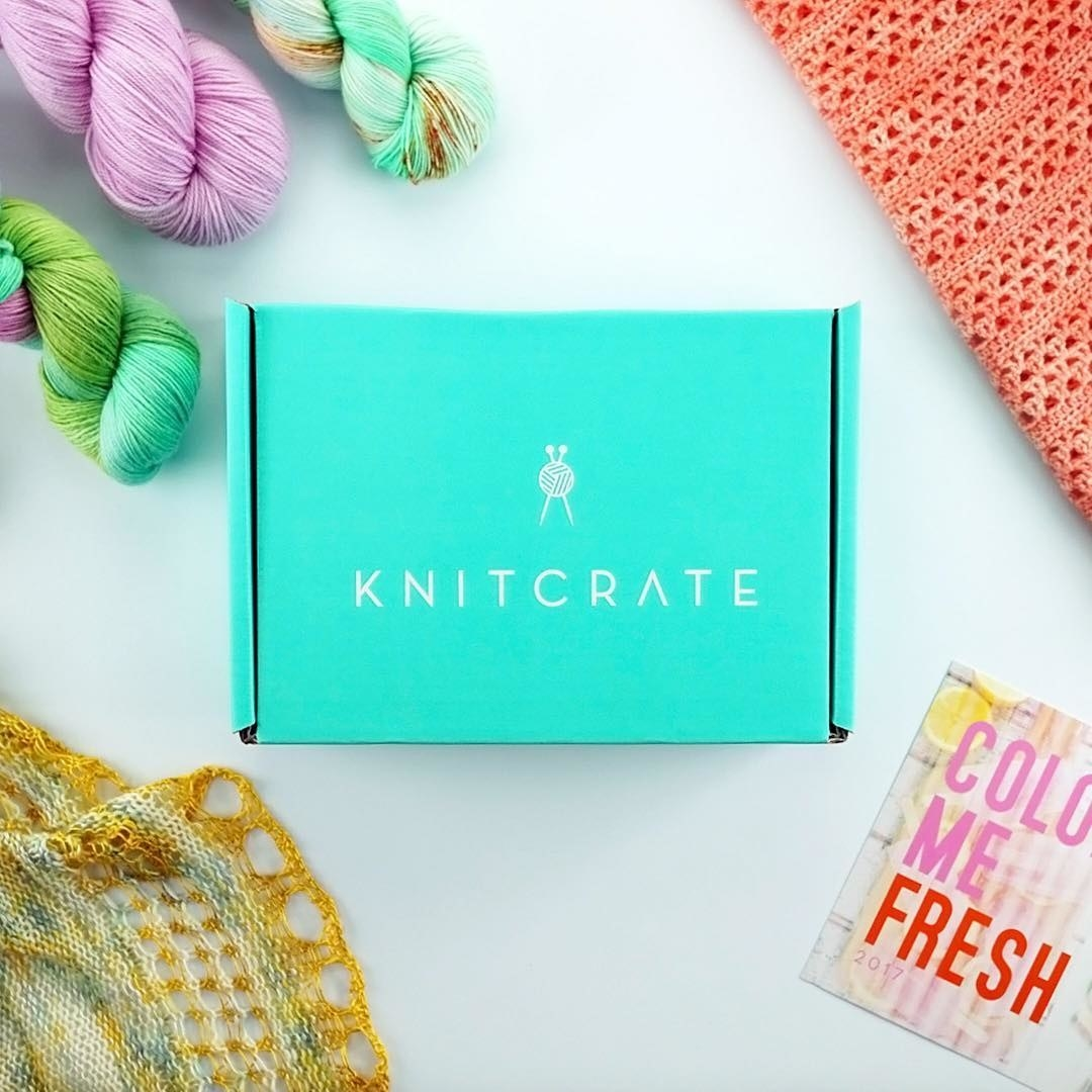 "Teal ""Knitcrate"" box surrounded by three colorful skeins of yarn, a knitting project and a crochet project."