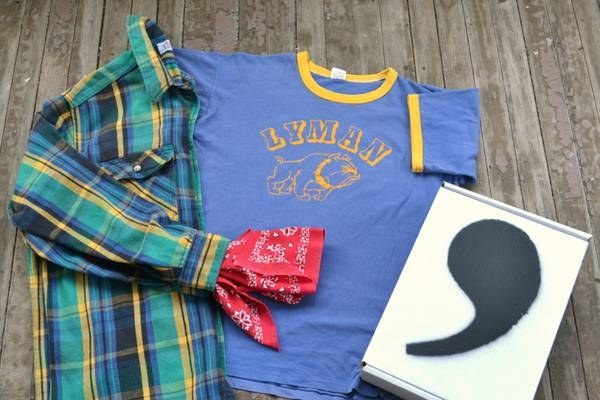 Flatlay with a comma vintage box, vintage ringer tee, plaid flannel, and red bandana.