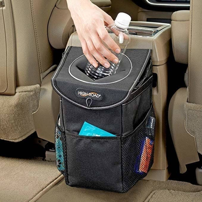 A mini trash can that connects the head rest or center console and has a lid to prevent everything from falling out