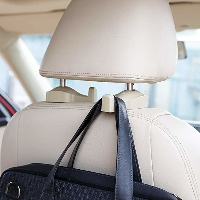 A purse hanging on the clip that's attached to the headrest