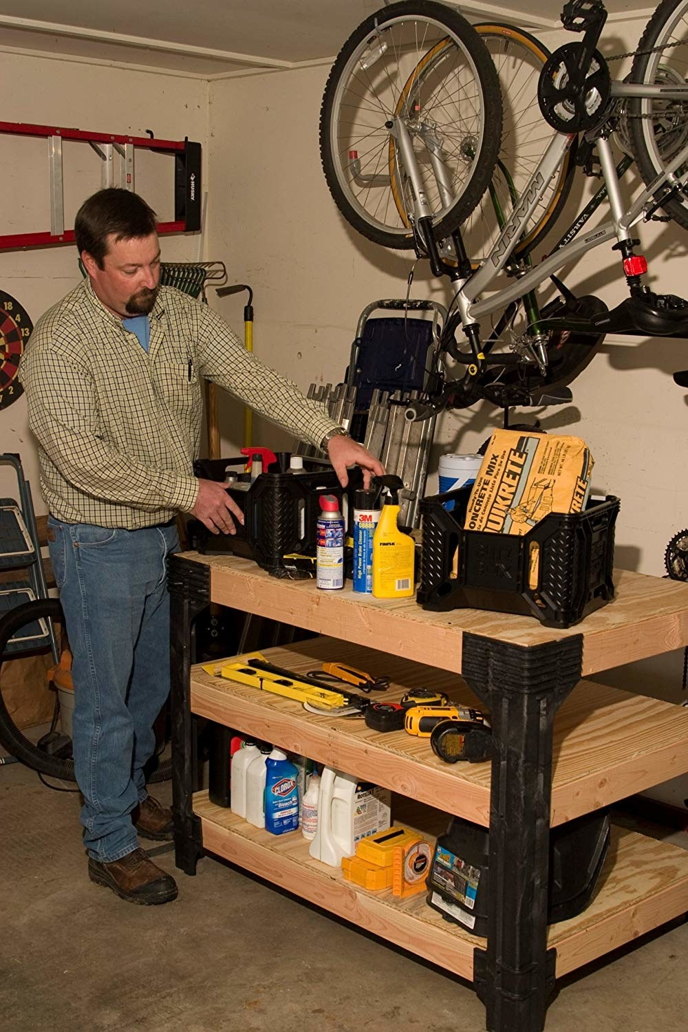 a model organizing his tools on the three tiers of the wooden workbench