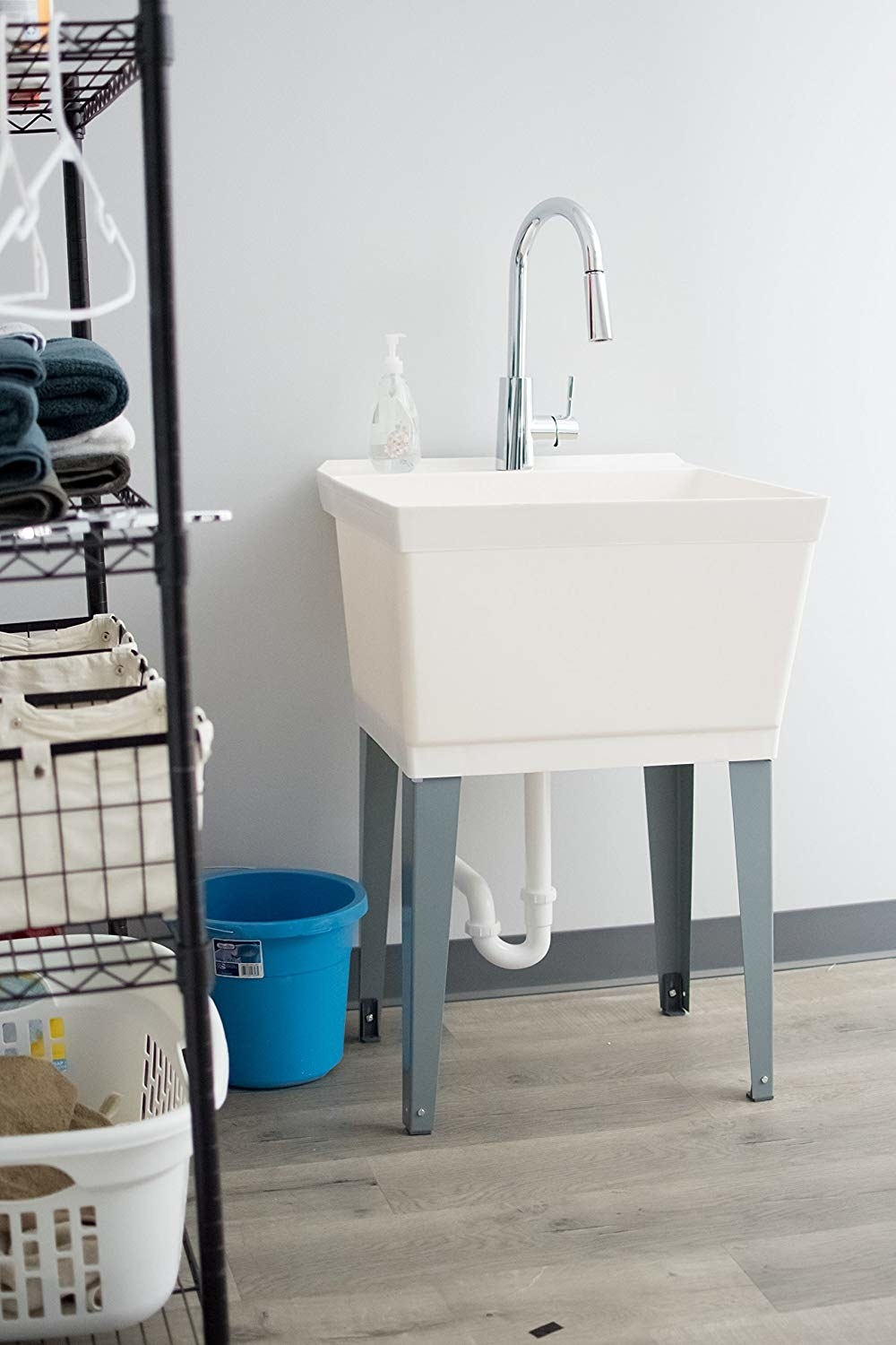 a white utility sink with four gray legs