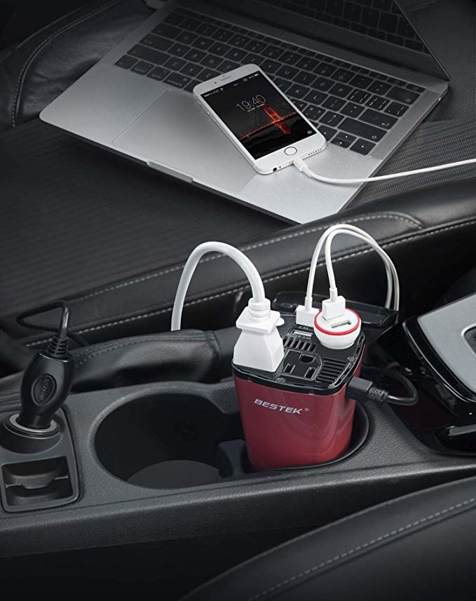 A photo of the car power converter in a cup holder of a car.