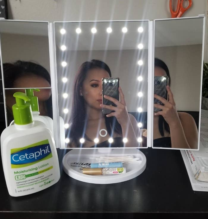 A reviewer taking a mirror selfie; the mirror is foldable with three panels, a tray to hold products, and lights all around the center panel