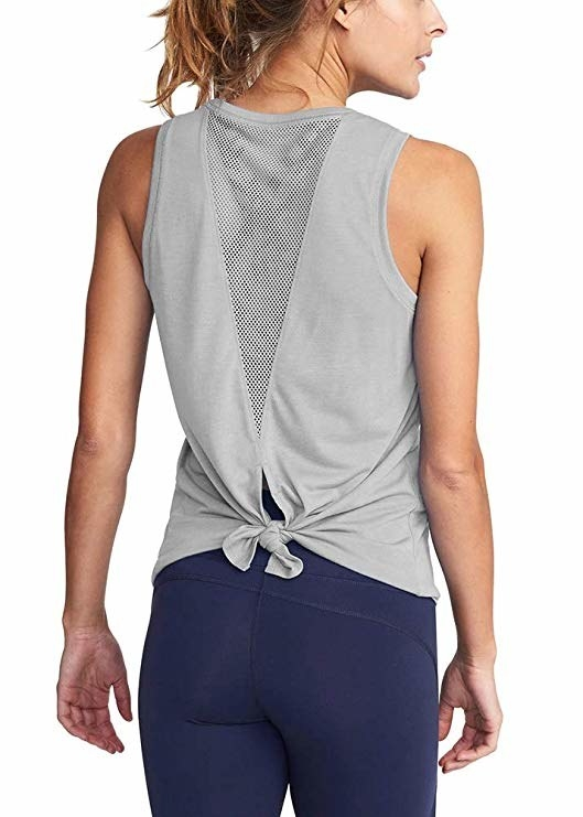 a model showing the back of the gray tank top with a mesh cutout in the center