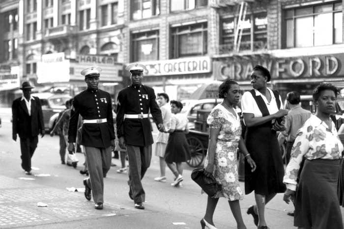 Two Marines walk down a street in Harlem, June 1943.