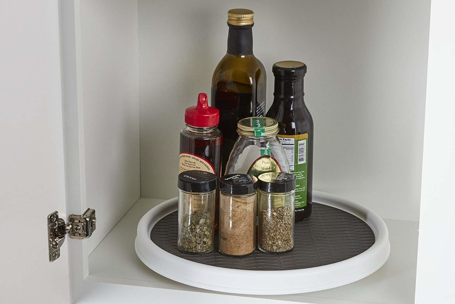 the lazy susan in cabinet with spices and condiments on it