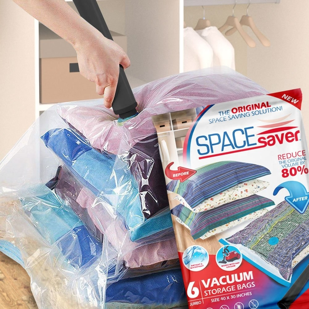 person vacuum sealing a bag filled with clothes