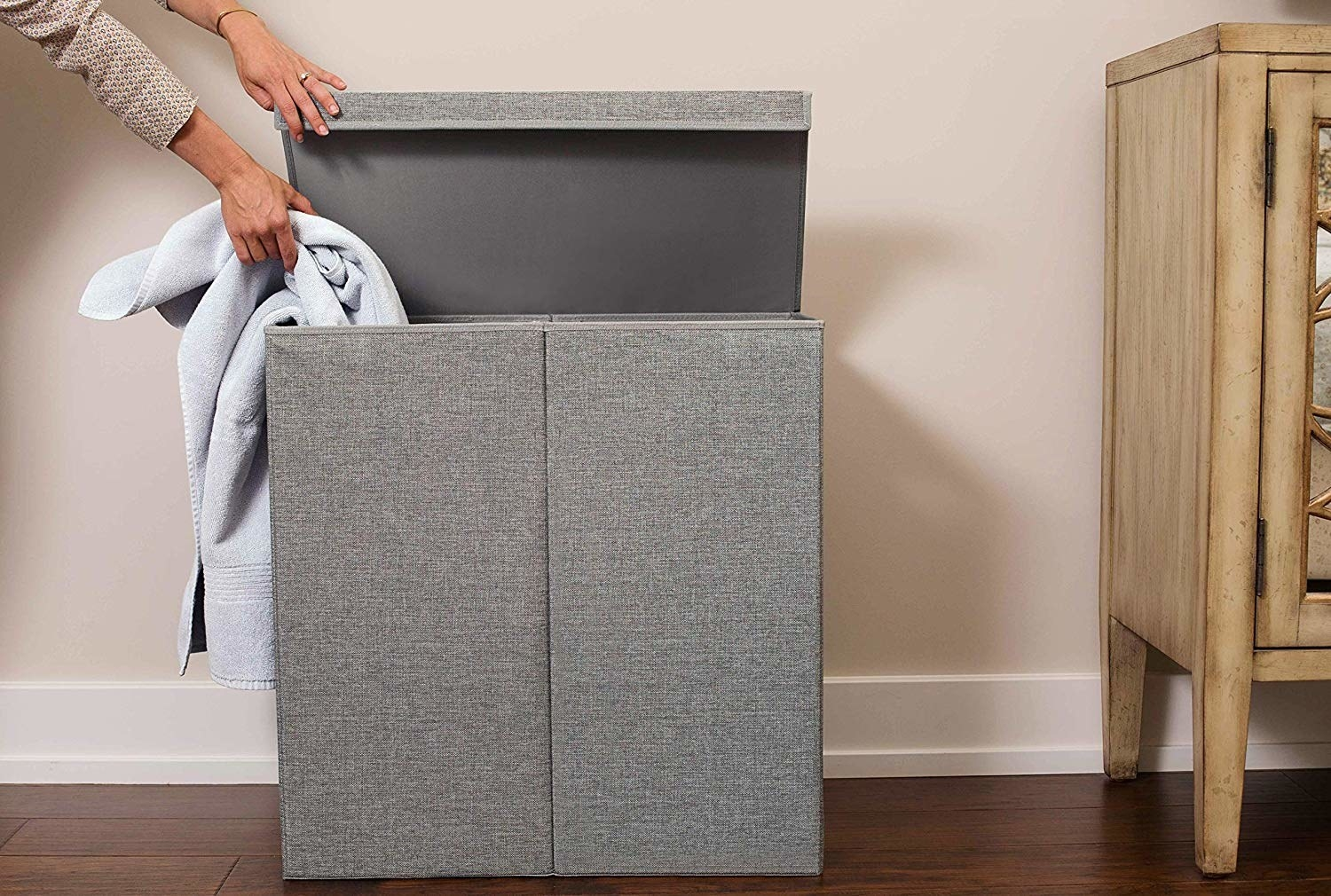 a person putting a towel into one side of the gray double hamper