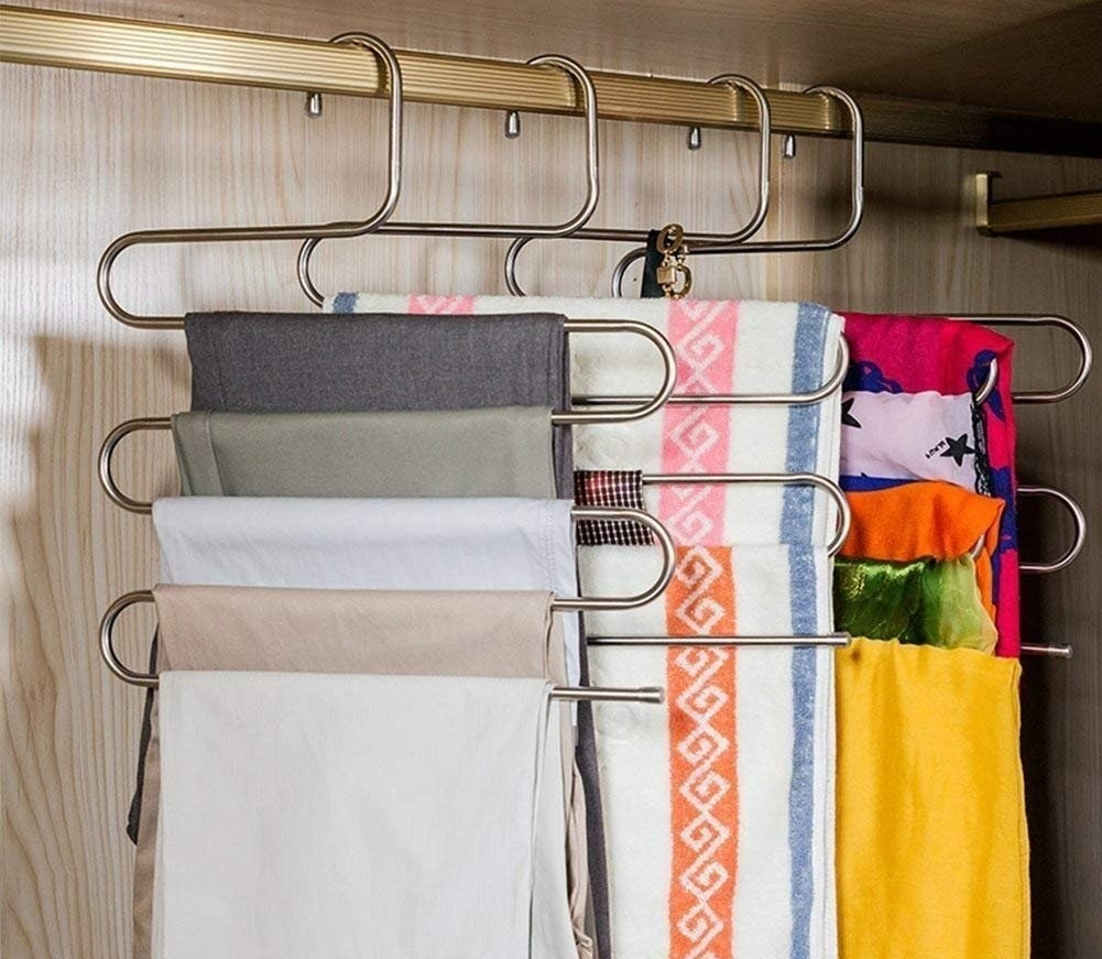 various s-shaped hangers holding multiple clothing items on them