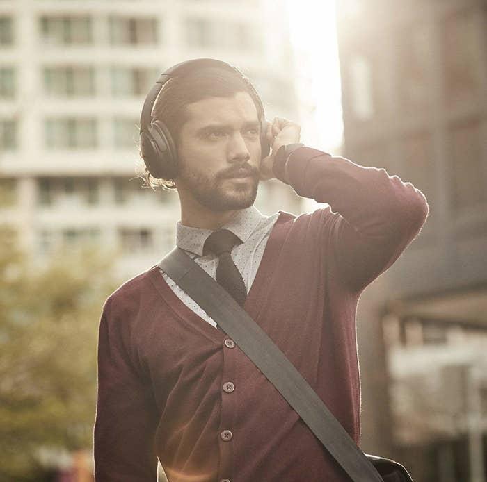 Model wearing the over-ear headphones in black