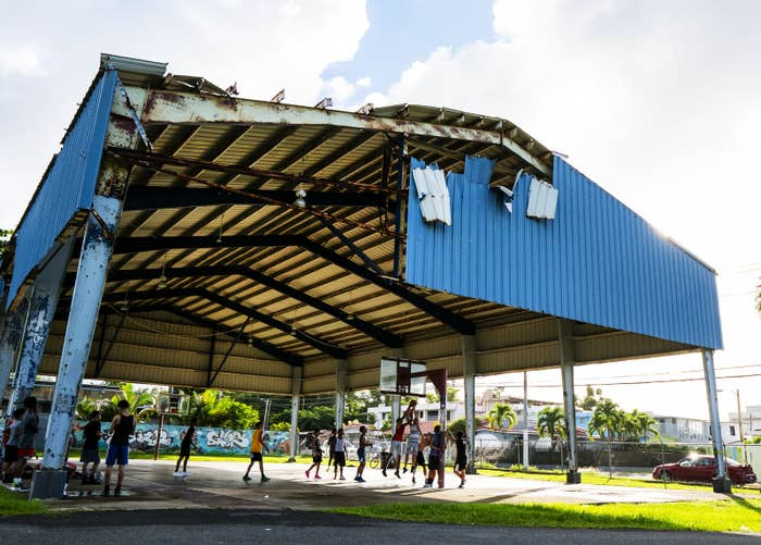 People play basketball under a heavily damaged open-air roof structure caused by Hurricane Maria in Puerto Rico.
