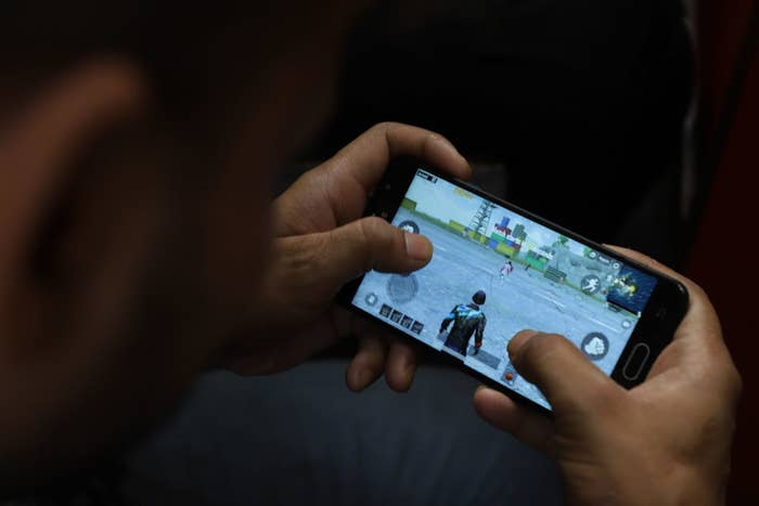 A young boy plays PUBG on his mobile phone at a restaurant in New Delhi on May 3.