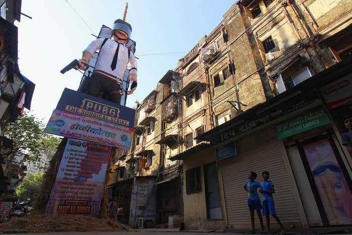 An effigy of a PUBG character is readied be set on fire as part of the Hindu festival of Holi in Mumbai on March 19. Representations of evil are burned on the holiday. The text on the board below warns people about PUBG's addictive effects.