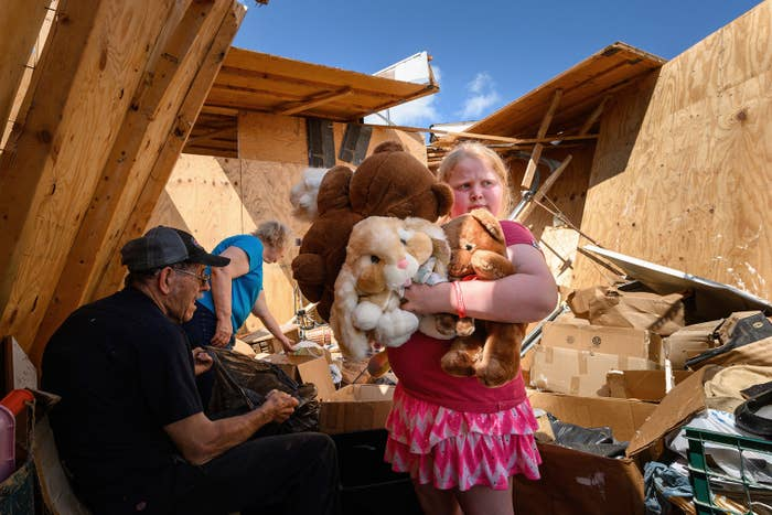 Keeley Frank, 9, holds stuffed animals her grandparents Al and Barb Scheidegger (left) salvaged from their storage unit May 23, in Jefferson City, Missouri, following a massive tornado in the area.