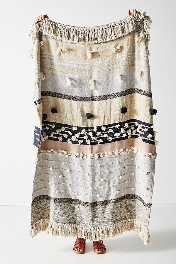 A blanket with tassels and pom poms of varying shapes, sizes, and colors