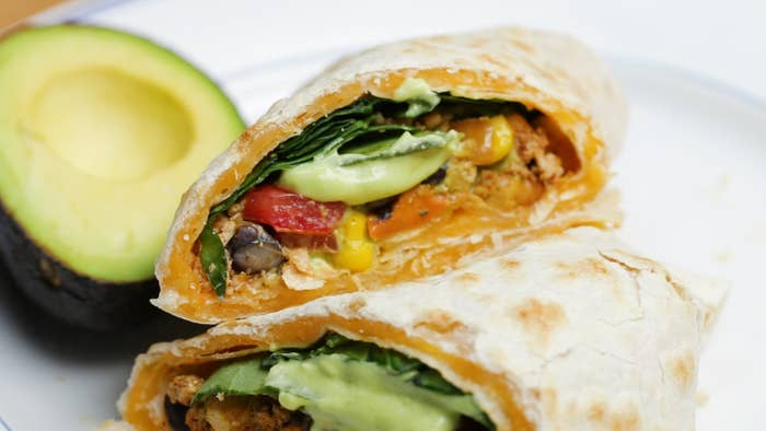 Servings: 4 INGREDIENTSAvocado Dressing1 avocadoJuice of 1 lime¼ cup olive oil3 cloves garlic½ teaspoon pepper½ teaspoon salt2 tablespoons waterQuesarito1 tablespoon olive oil, plus more as needed½ cup diced white onion2 cloves garlic7 ounces (200 grams) extra firm tofu, crumbled¼ teaspoon smoked paprika1 teaspoon chili powder½ teaspoon cumin2 teaspoons soy sauce1 medium sweet potato, peeled and diced¾ teaspoon salt, divided¾ teaspoon pepper, divided1 15-ounce can chickpeas, drained and rinsed1 teaspoon garlic powder1 teaspoon chili powder8 large flour tortillas2 cups shredded cheese blend2 cups fresh spinach1 cup diced tomatoes1 cup black beans1 cup cornPREPARATIONMake the avocado dressing: in a blender, combine the avocado, lime juice, olive oil, garlic, pepper, salt, and water, and blend until smooth.Heat the olive oil in a large skillet over medium-high heat. Add the onion and sauté until translucent, 3 minutes. Add the garlic, tofu, paprika, cumin, and chili powder, and stir to combine. Add the soy sauce, stir, and cook for 3 minutes more, until tofu mixture is evenly heated.Transfer the tofu to a medium bowl and set aside.Add more oil to the pan if needed, then add the sweet potatoes, ½ teaspoon salt, and ½ teaspoon pepper. Stir, cover, and cook for about 5 minutes, until sweet potatoes are tender.Remove the sweet potato from the pan and set aside.Add the chickpeas, garlic powder, chili powder, remaining ¼ teaspoon salt, and remaining ¼ teaspoon pepper. Stir and cook for about 5 minutes, until the chickpeas are crispy.Remove chickpeas and set aside.Reduce the heat to medium-low, add a tortilla to the pan and sprinkle with ½ cup cheese, then cover with another tortilla. Cook until the cheese melts, about 3 minutes, flipping once halfway through. Repeat with the remaining tortillas and cheese.Transfer the tortillas to plates and fill with with spinach, tofu, tomatoes, black beans, corn, sweet potatoes, and chickpeas. Drizzle with avocado dressing.Fold in the lef