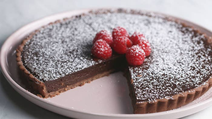Servings: 8 IngredientsTart Dough ½ cup (1 stick) unsalted butter, softened ½ cup powdered sugar1 large egg, room temperature1½ cups all-purpose flour2 tablespoons cocoa powder ¼ teaspoon salt Filling⅓ cup water½ cup (1 stick) butter1 teaspoon instant coffee1 cup chopped dark chocolate⅓ cup sugar1 tablespoon vanillaPinch of salt3 large eggs Fresh raspberries, for servingPowdered sugar, for serving PreparationMake the tart dough: add the butter to a medium bowl and sift in the powdered sugar through a fine-mesh sieve. Using an electric hand mixer, beat until smooth. Beat the egg and add half at a time to the butter mixture, beating well to incorporate between additions.Sift in the flour and cocoa powder, and add the salt. Using a rubber spatula, mix the dough until the cocoa powder is evenly distributed. Wrap the dough in plastic wrap and chill in the refrigerator for at least 30 minutes, or overnight (if you chill the dough overnight, let it sit at room temperature for 15-30 minutes before rolling out).Preheat the oven to 375˚F (190˚C). Grease a 9-inch tart pan and roll out the chilled dough to an 11-inch circle. Roll the dough around the rolling pin, then unroll the dough over the pan. Press the dough against the bottom and sides of the pan, then use the rolling pin to roll over the top of the pan, cutting off any excess dough (re-roll any excess dough and bake into cookies, if desired). Press the dough gently against the pan once more. Using a folk, prick some holes in the bottom of the crust so it doesn't puff up. Bake for 15 minutes, then remove the tart shell from the oven and reduce the temperature to 300˚F (150˚C)Make the filling: in a medium saucepan, heat the pan over high heat. Combine the water and butter, and bring to a boil. Add the instant coffee and stir until dissolved. Add the chocolate, sugar, and vanilla to a medium bowl and pour the hot butter mixture over. Whisk until the chocolate is melted and the mixture is glossy.Add the eggs and whisk well 