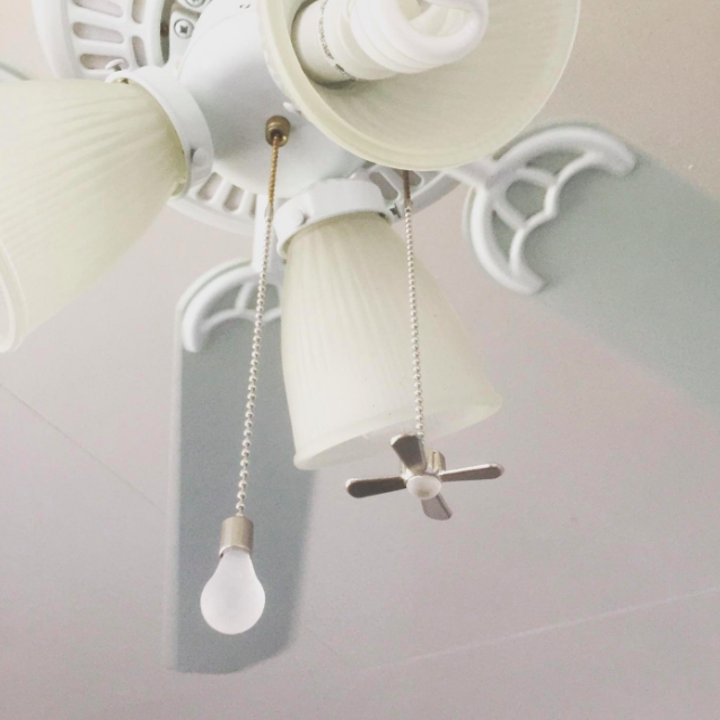 a ceiling fan with the pull chains attached