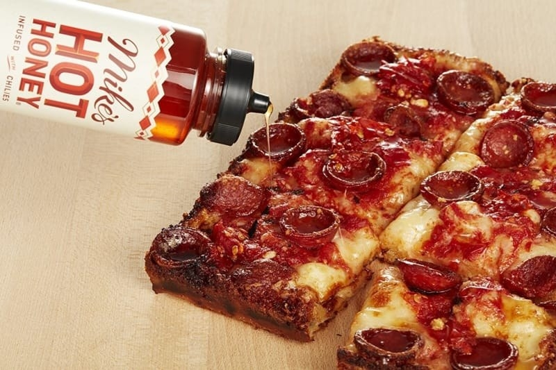 A bottle of Mike's Hot Honey being drizzled over a pepperoni pizza