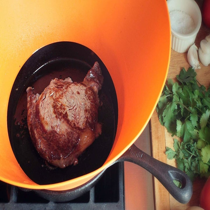 An orange frywall placd in a pan that is cooking food in sauce