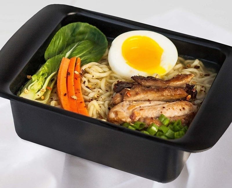 A black ramen noodle cooker with prepared ramen noodles and toppings like meat, vegetables, and, an egg