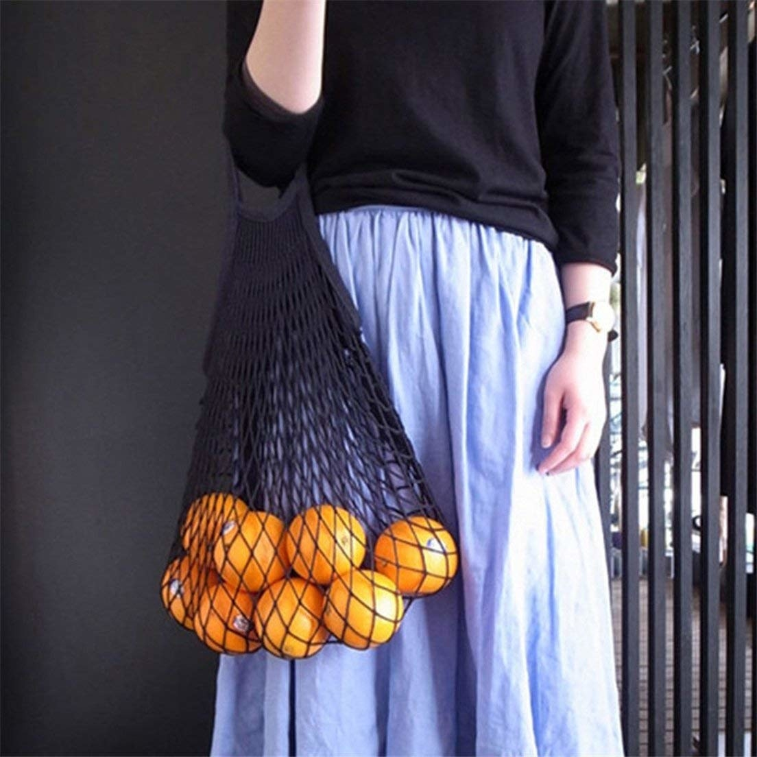 A person holding the net grocery bag filled with oranges