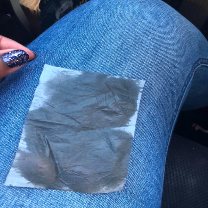 A reviewer showing the used tissue with oil all over it