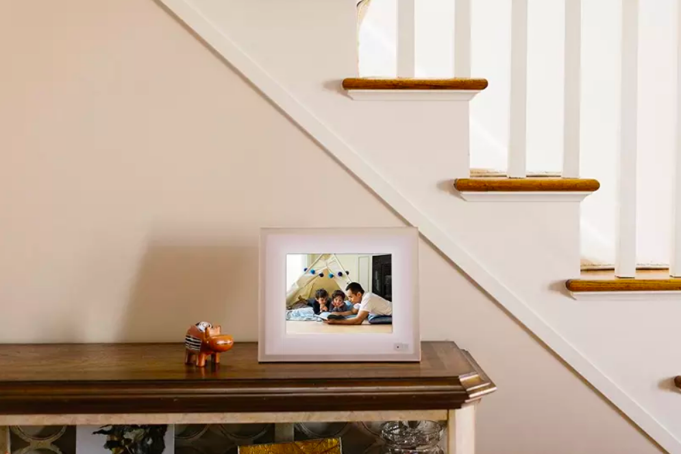 A lifestyle shot of the picture frame on an entryway table, showing an image of a family of three