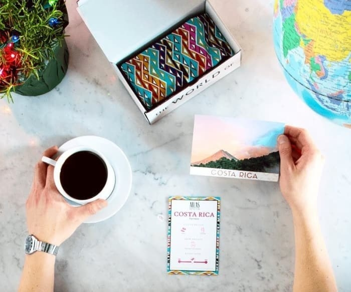 Table with a small box filled with a coffee bean bag, hand around a cup of coffee, another hand holding a postcard that cast Costa Rica